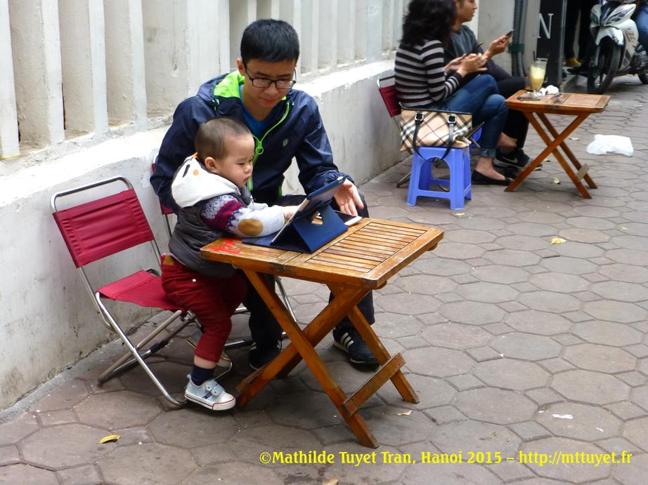 Un petit garçon apprend à utiliser la tablette de son jeune papa sur le trottoir, au café trottoir. ©Mathilde Tuyet Tran, Hanoi 2015 – http://mttuyet.fr